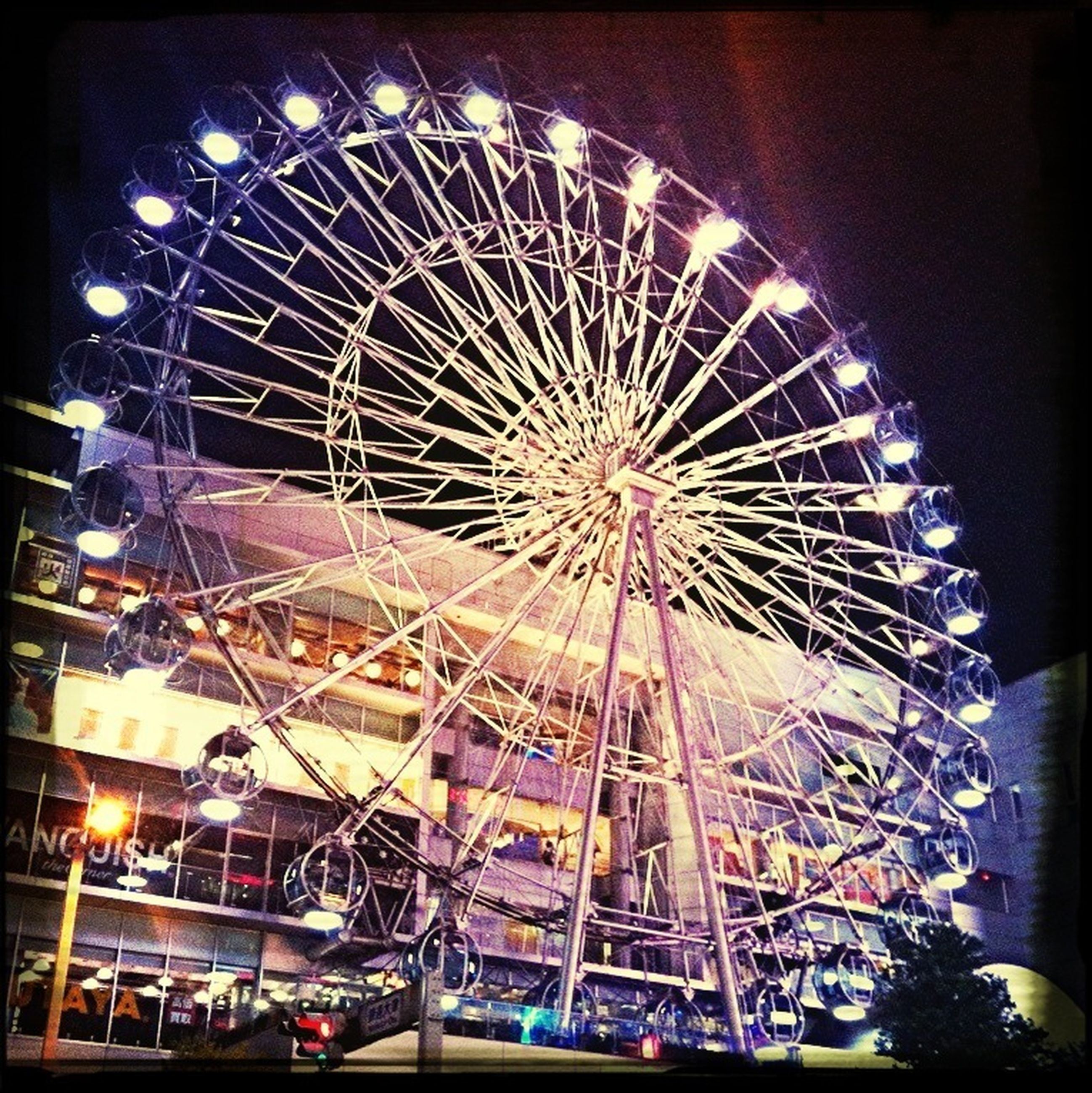arts culture and entertainment, amusement park, amusement park ride, ferris wheel, transfer print, night, illuminated, low angle view, sky, built structure, incidental people, auto post production filter, fun, enjoyment, architecture, motion, traveling carnival, outdoors, leisure activity, big wheel