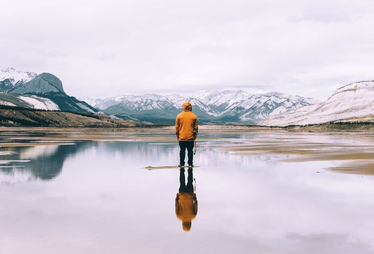 Rear View Of Man Standing Amidst Lake By Snowcapped Mountains