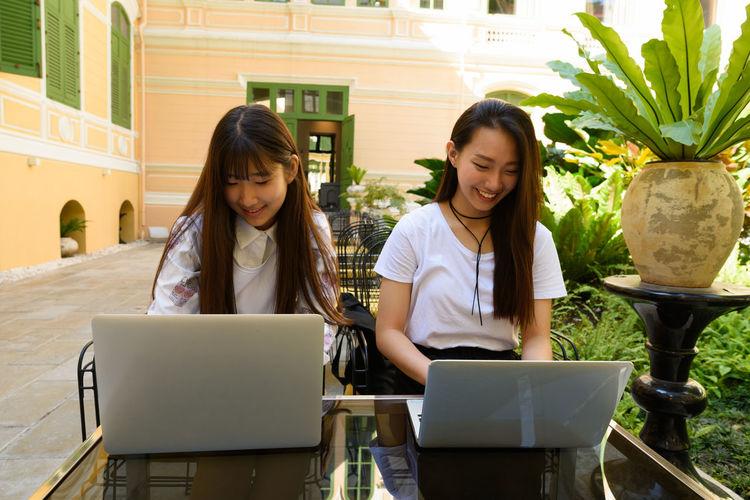 Smiling women using laptop outdoors