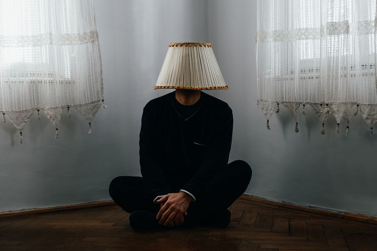 Man wearing lamp shade while sitting on floor