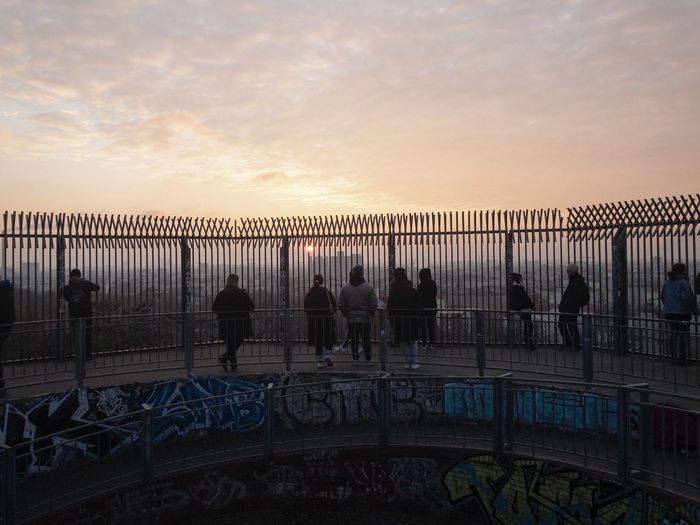 People on railing against sky during sunset
