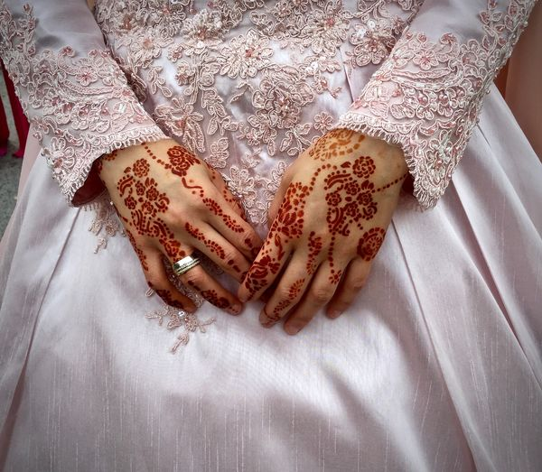Midsection of woman with henna tattoo on hand