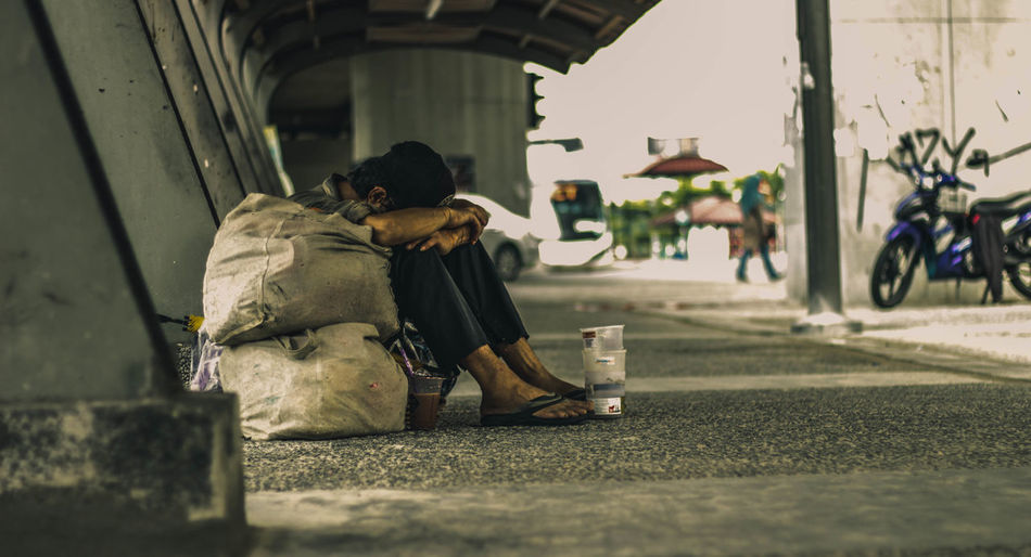Beggar Sitting Under Bridge