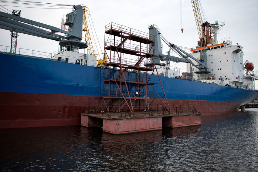 The ship hull painting works. Cranes Harbor Heavy Industry Transport Boats Docks Equipment Export Import Load Logistic Material Port Repair Scrap Sea Seaside Steel Storage Terminal Transshipment Terminal Unload Vessel