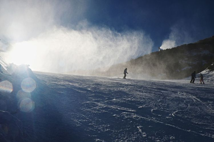 Snowmaking on slope. skier near a snow cannon making fresch powder snow. ski resort and winter