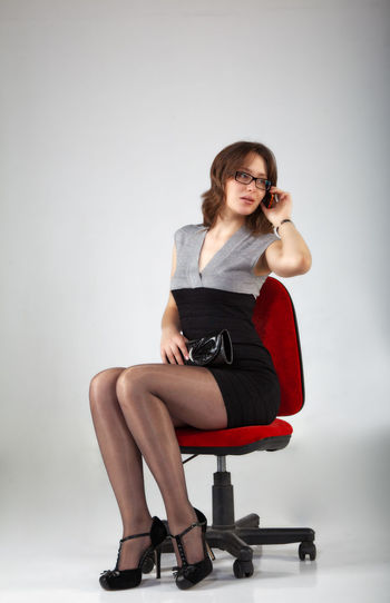 Full Length Of Beautiful Woman Talking On Mobile Phone While Sitting On Chair Against Gray Background