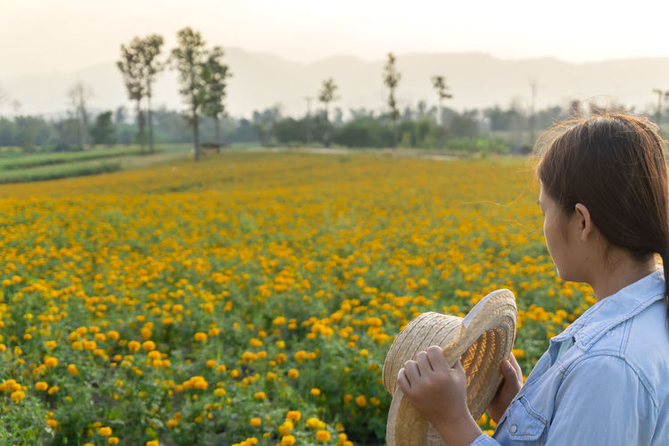 Marigold Portrait Flower Marigold Flower Farmer Selective Focus Lifestyles Outdoors Nature Plant Leisure Activity Care Check One Person Yellow Field Real People Beauty In Nature Flowering Plant Growth Rear View Freshness Land Waist Up Focus On Foreground Child Hairstyle