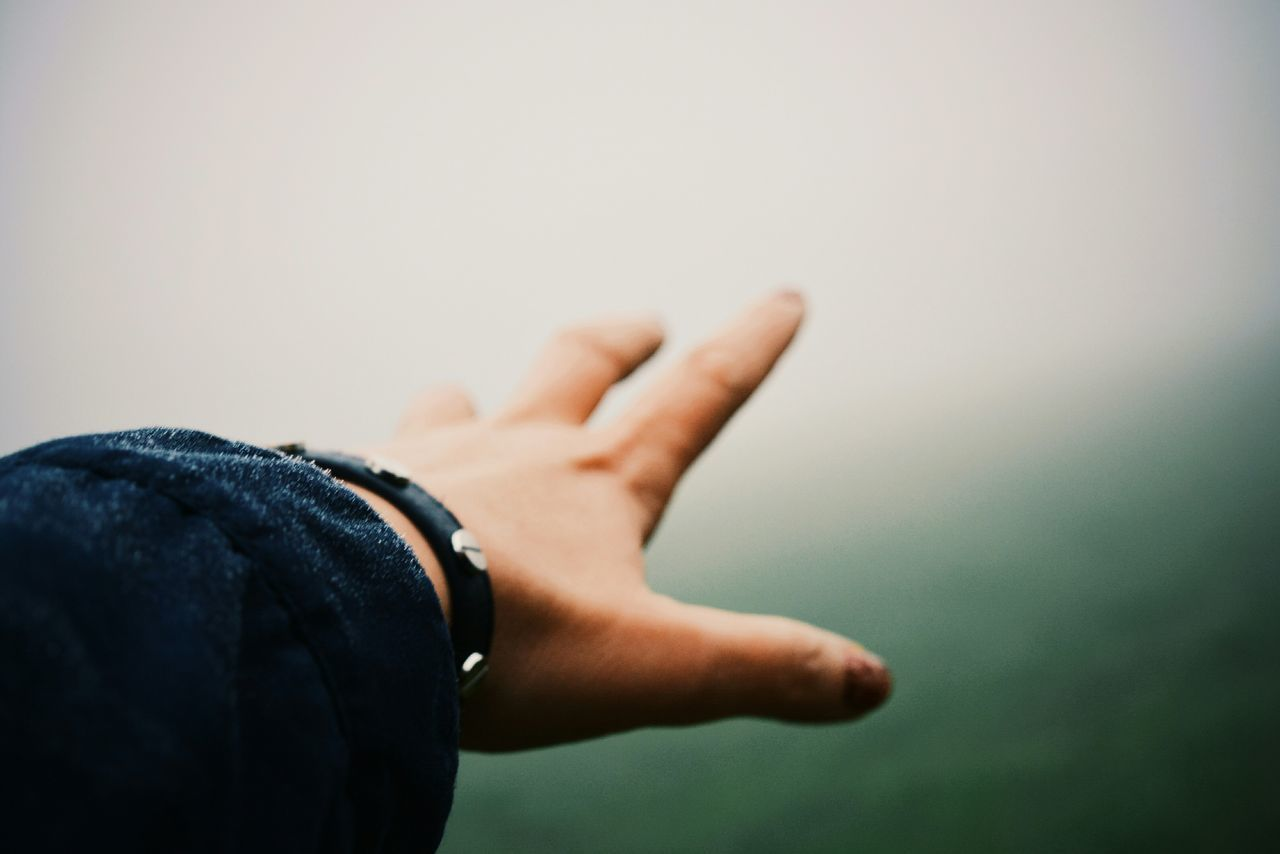 Cropped image of person hand against sky during foggy weather