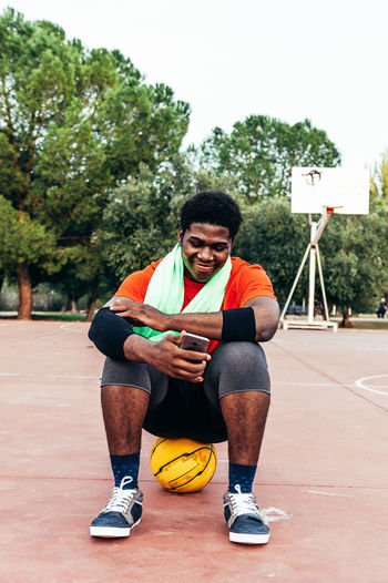 Full length of basketball player using mobile phone while sitting at court