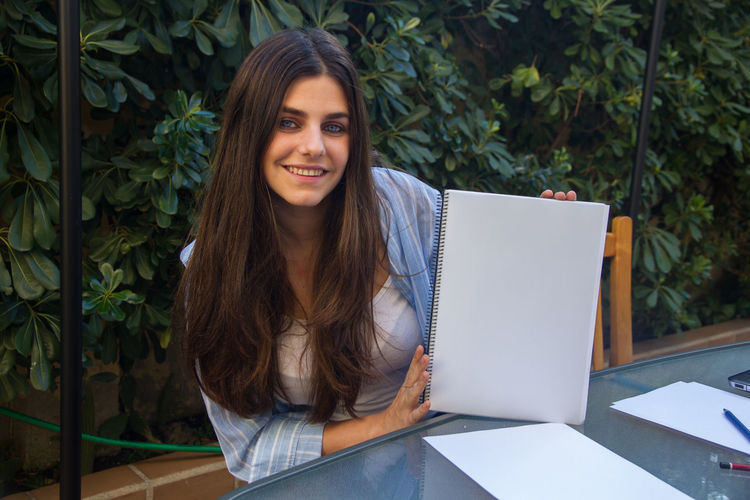 Portrait of smiling woman holding spiral notebook against plants