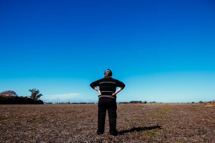 Woman standing on land against clear blue sky