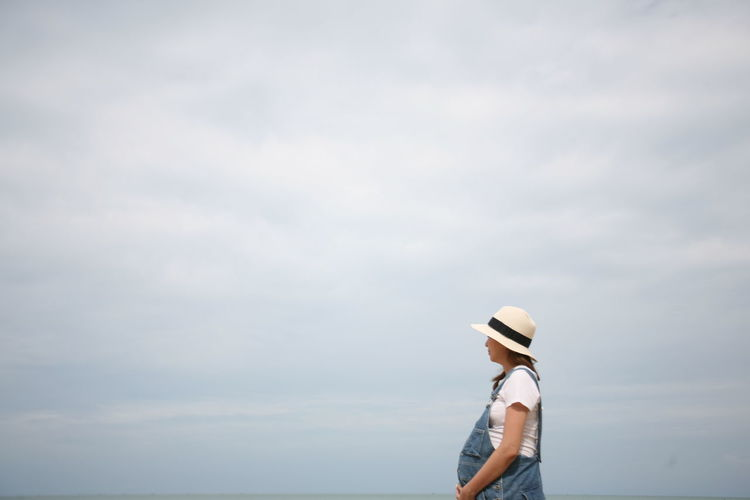Side view of pregnant women standing against sky
