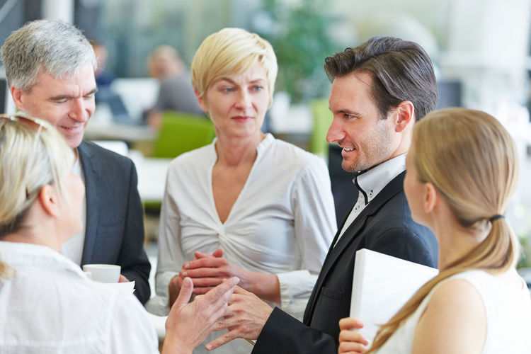 Business people discussing while standing in office