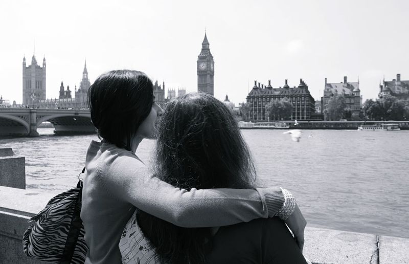 Mother and daughter by thames river against big ben on sunny day