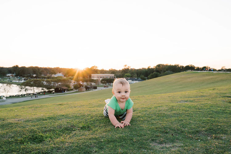 Boy on field against sky during sunset