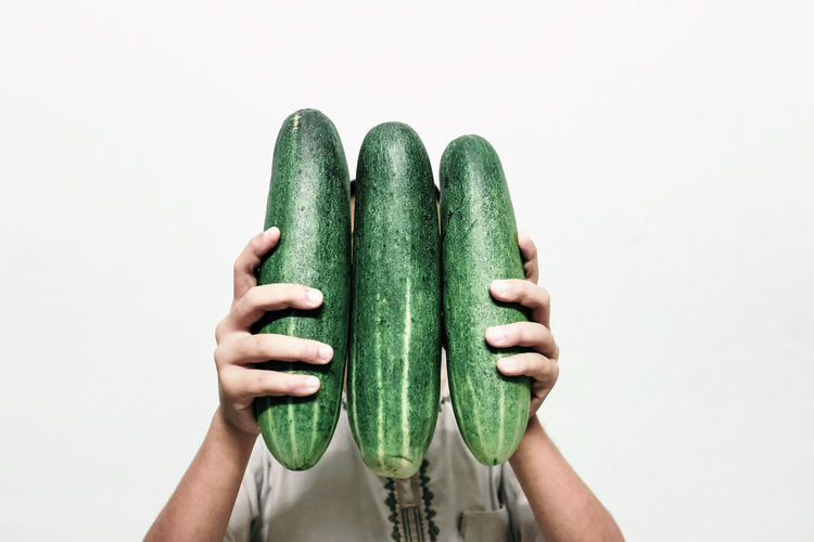 Woman holding cucumber against white background