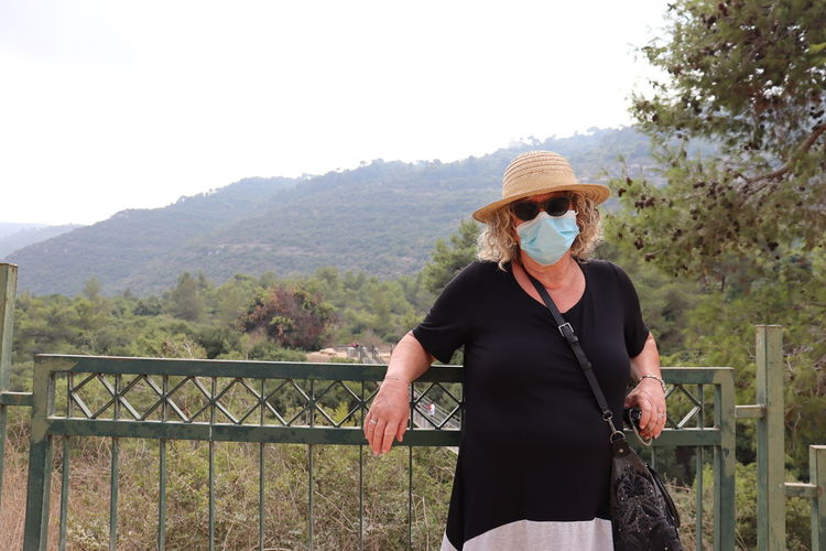 Woman standing on railing against mountain