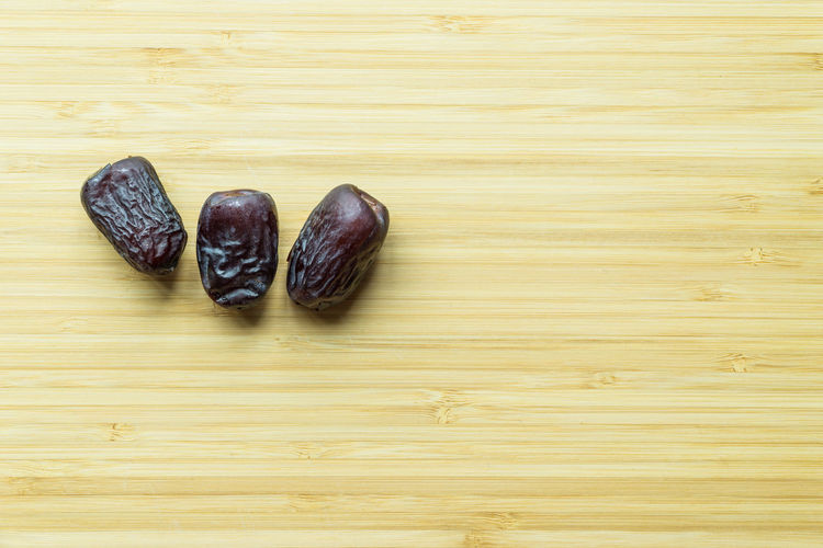 Dates or kurma over wooden background Close-up Dates Fasting Food Freshness Kurma Muslim No People Ramadhan Top View