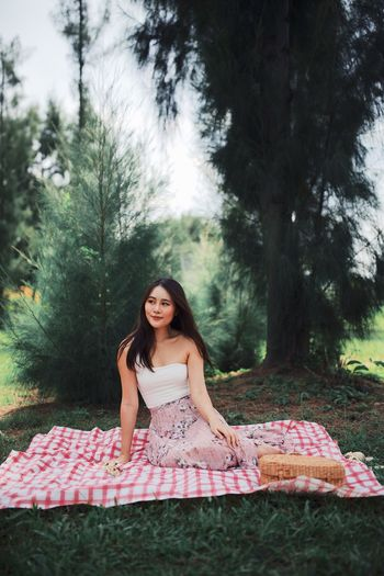 Young woman looking away while sitting on picnic blanket against trees