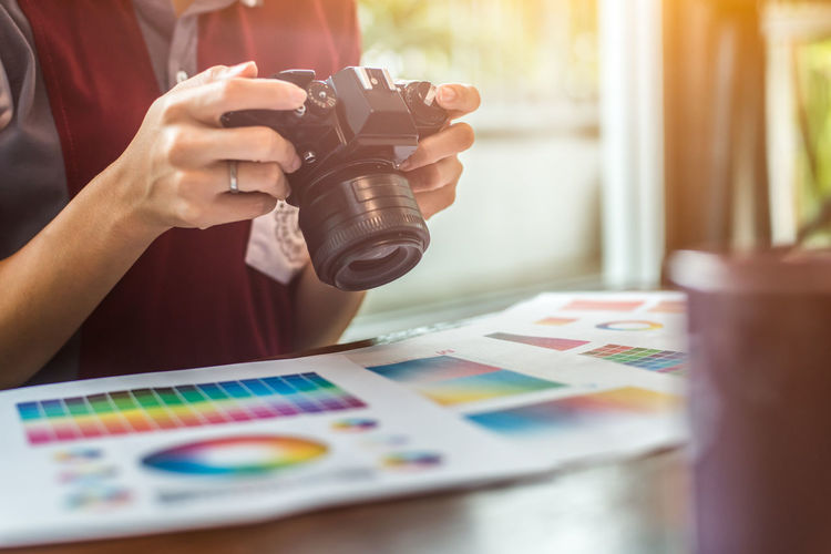 Midsection of woman photographing color swatch on table