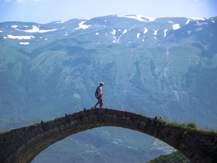 Woman walking with daughter on bridge by mountain against sky