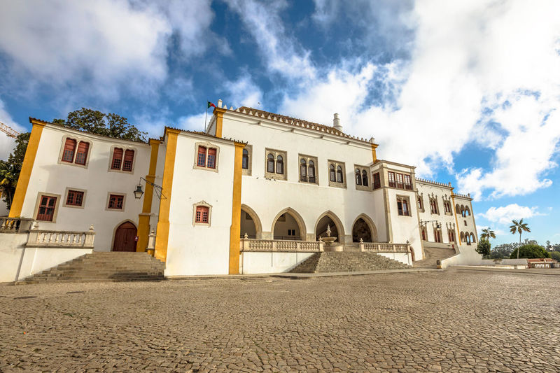 Panoramic aerial view of National Palace of Sintra or Town Palace, in Portuguese Palacio Nacional de Sintra, with two white famous chimneys rising out of palace. Sintra, Portugal. Unesco Heritage Site Sintra City Portugal Cityscape Skyline Palacio Nacional De Sintra Palace Aerial View Castle Tourist Architecture Built Structure Cloud - Sky Building Exterior Sky Arch Building Nature No People Day Low Angle View Outdoors History The Past Residential District Façade Window Travel Destinations Direction Surface Level Luxury Arched Courtyard