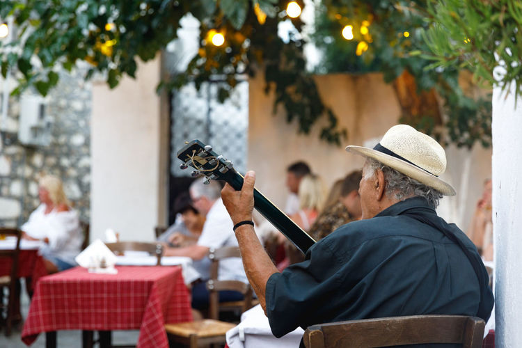 Rear View Of Man Playing Guitar While Sitting On Chair At Outdoor Restaurant