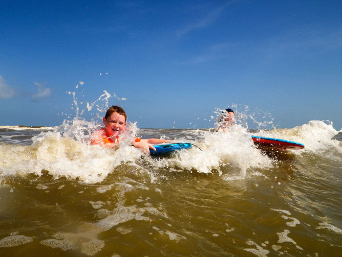 Beach Boogie Boarding  Carefree Enjoyment Fun Gulf Of Mexico Innocence Port Aransas Real People Recreational Pursuit Rippled Sea Seaside Water Wave Photography In Motion