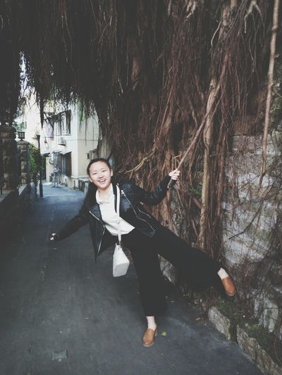 Portrait of cheerful woman holding banyan tree vine on footpath