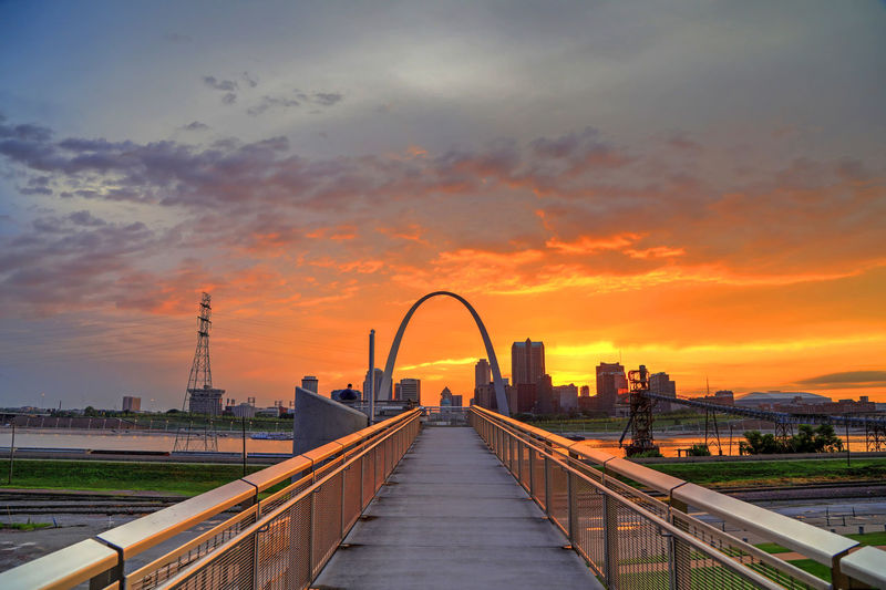 Bridge Over River And Buildings Against Sky During Sunset