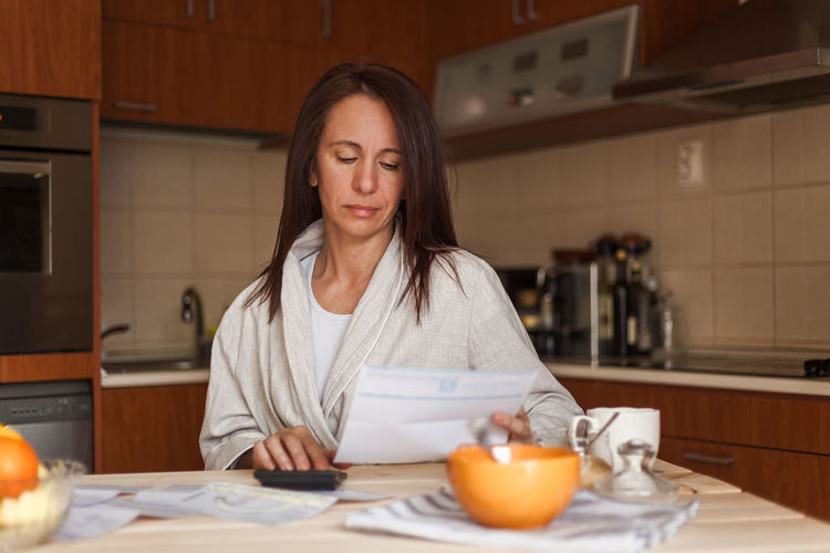 Woman reading document while having breakfast at home