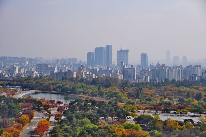 View of modern buildings in city against sky during autumn