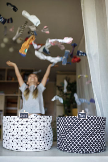 Girl throwing clothes mid air at home