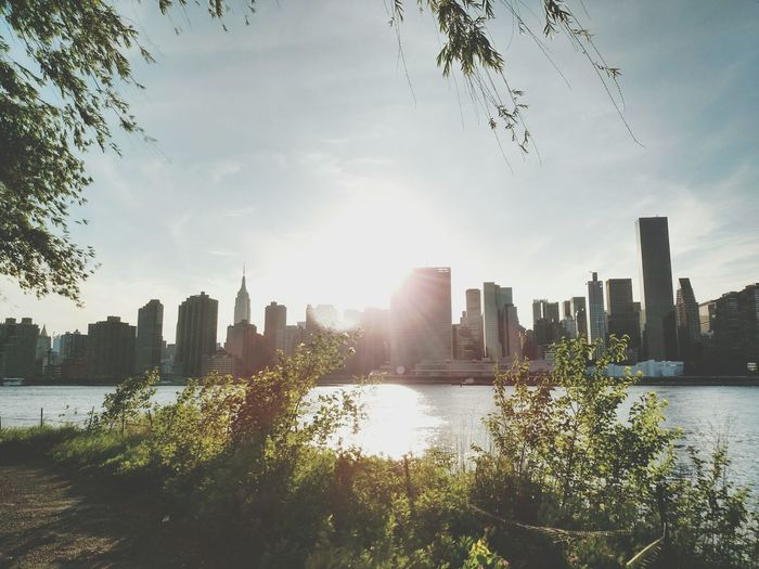 Urban Skyline By River Against Sky