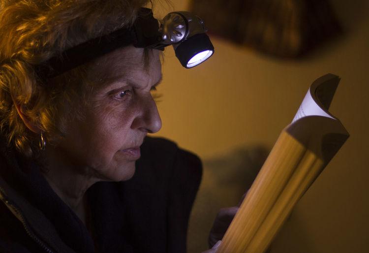 Close-up of senior woman reading book at home