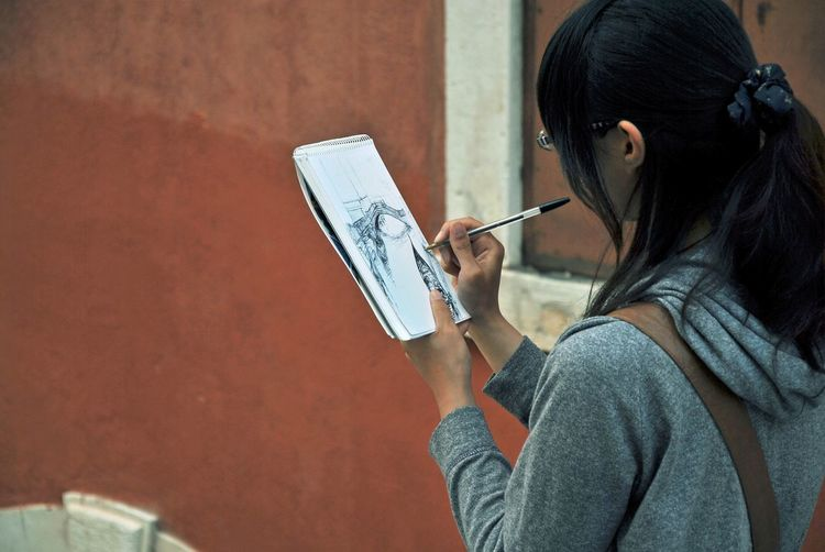 Side View Of Artist Drawing In Note Pad