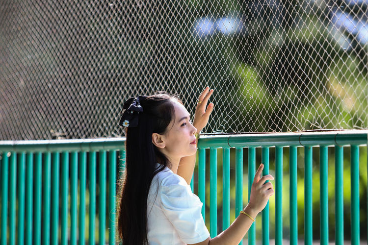 Portrait of a young woman standing against fence