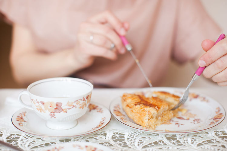 Midsection of woman having breakfast on table