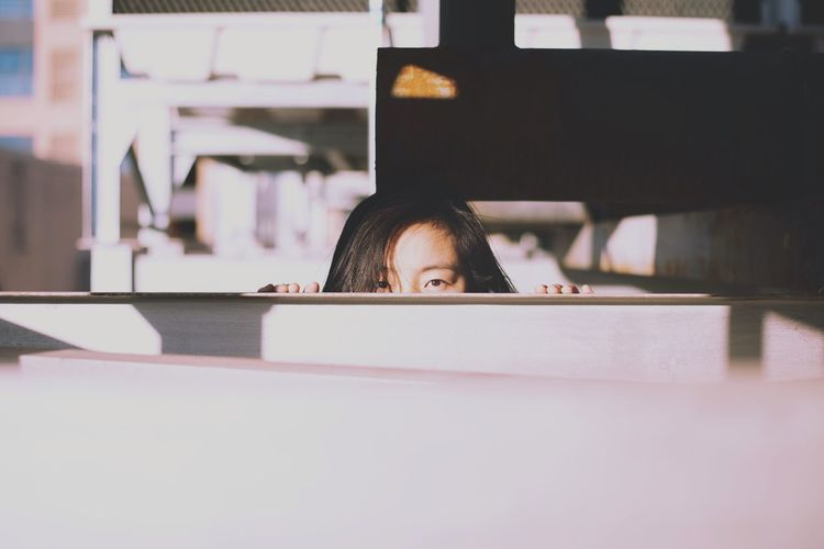 Portrait of a girl hiding behind table