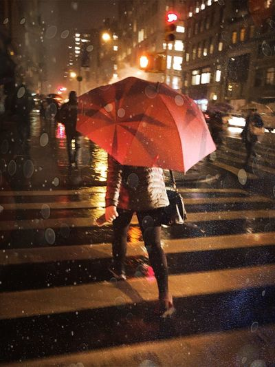 Low section of woman with red umbrella walking on road during rainy season
