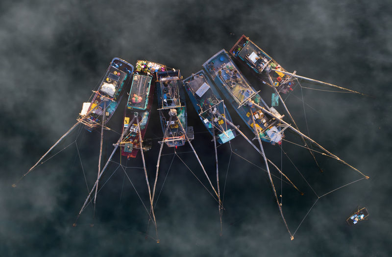 Directly above shot of fishing boats in sea during foggy weather