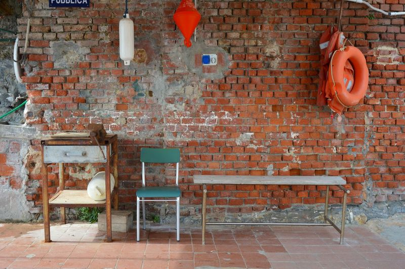 Empty chair and tables against brick wall