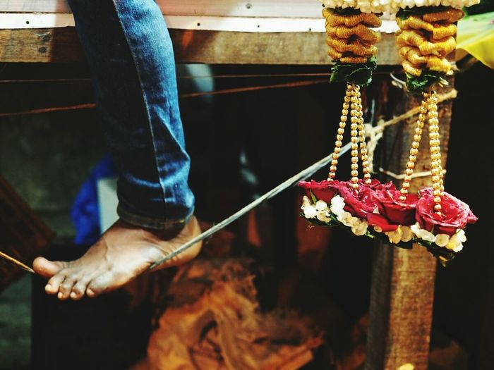 Close-Up Of Hanging Garlands And Human Feet On String