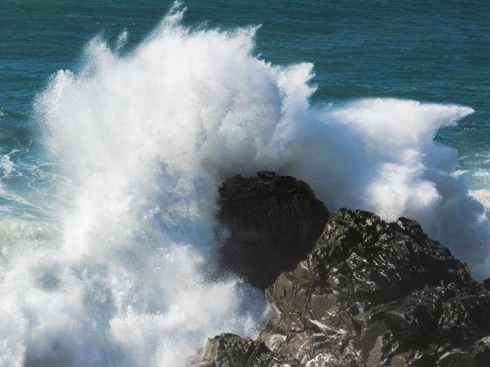 High angle view of waves crashing on rocks at shore