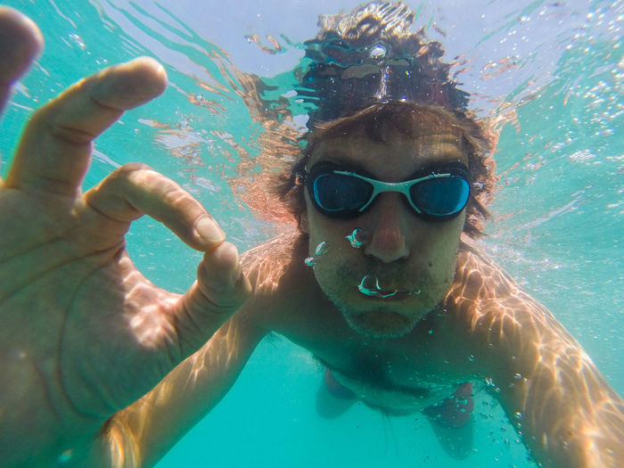 Portrait of man gesturing ok sign while swimming in sea