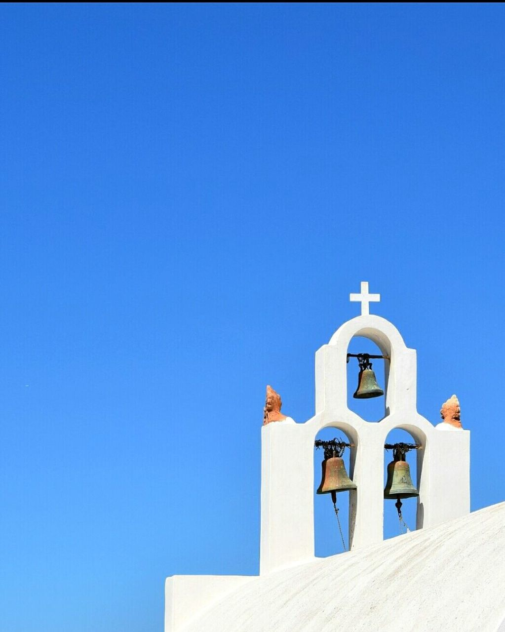 religion, clear sky, copy space, blue, white color, built structure, day, spirituality, low angle view, place of worship, outdoors, architecture, no people, whitewashed, bell, cross, summer, sunlight, bell tower, building exterior, nature, sky