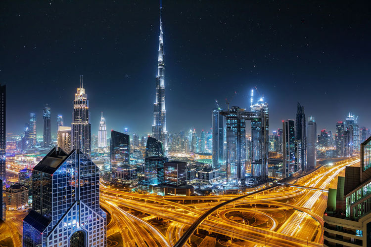Illuminated burj khalifa amidst buildings in elevated road at night