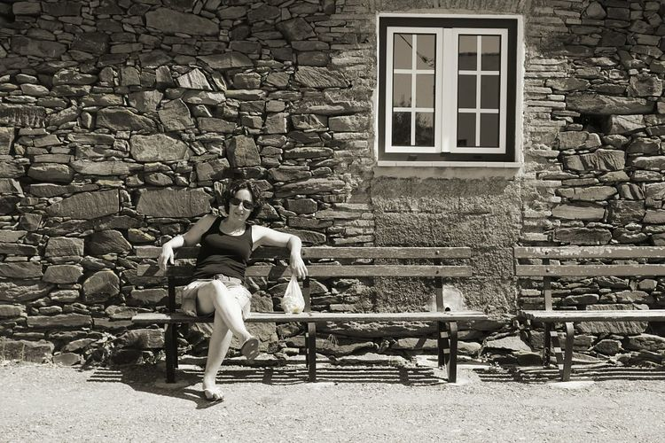Full length of woman sitting on bench by old house