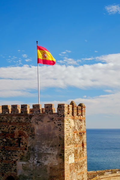 the spain flag on the fortress SPAIN Spain Flag Architecture Beauty In Nature Blue Building Exterior Built Structure Cloud - Sky Day Flag Fortress Fortress Of Stone Fortress Wall Horizon Over Water Nature No People Outdoors Sea Sky Water
