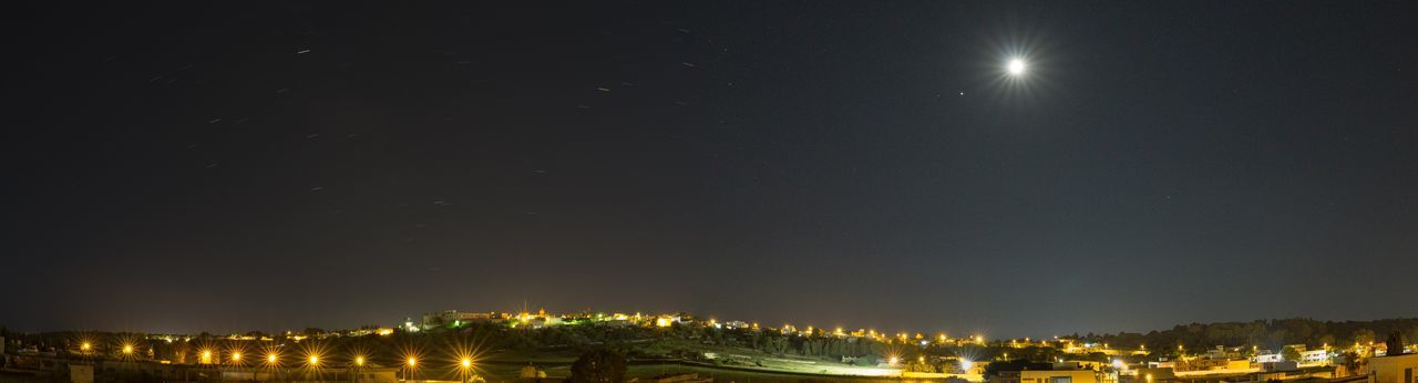 Panoramic view of illuminated buildings against sky at night